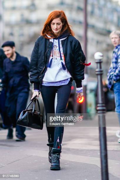 A guest wears a bomber jacket a hoodie a white sweater pants blue and white stripes sneakers shoes has red hair outside Proenza Schouler during Paris...
