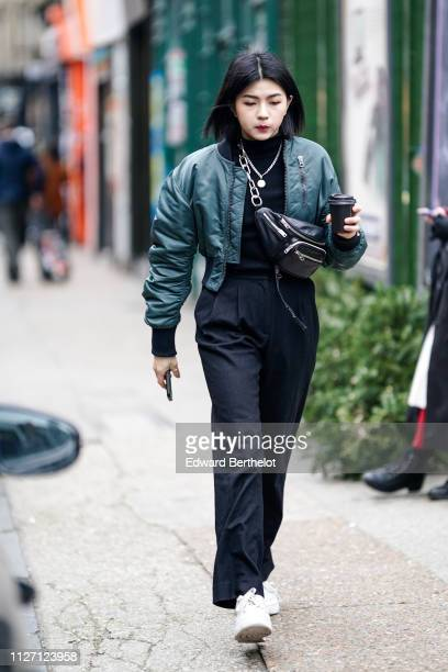 A guest wears a bomber jacket a shoulder strapped fanny pack bag black flare pants white sneakers shoes during London Fashion Week Men's January 2019...