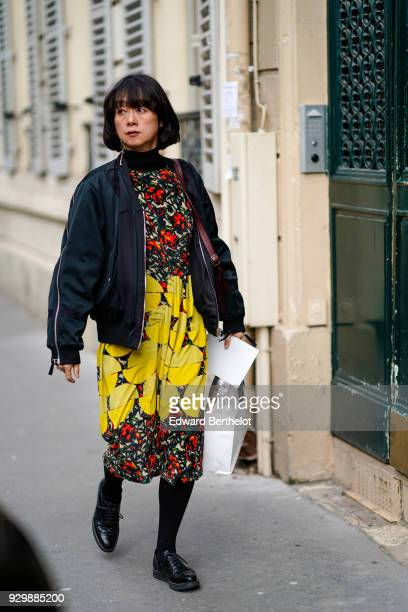 A guest wears a bomber jacket a yellow flower print dress black shoes outside APC during Paris Fashion Week Womenswear Fall/Winter 2018/2019 on March...