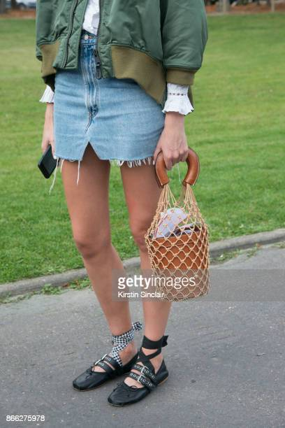 A guest wears a bomber jacket vintage denim skirt Miu Miu shoes and a Staud bag day 2 of Paris Womens Fashion Week Spring/Summer 2018 on September 27...