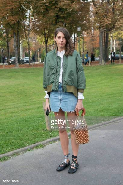 Guest wears a bomber jacket, vintage denim skirt, Miu Miu shoes and a Staud bag day 2 of Paris Womens Fashion Week Spring/Summer 2018, on September...