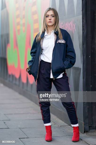 A guest wears a bomber jacket with checked lining a white shirt red shoes during London Fashion Week Men's January 2018 at on January 7 2018 in...