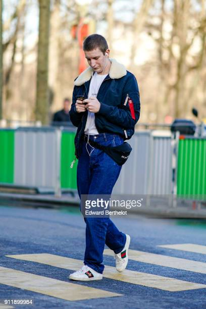 A guest wears a bomber jacket with sheep wool blue pants Gucci sneakers a white tshirt is sending a text message with a smartphone outside Chanel...