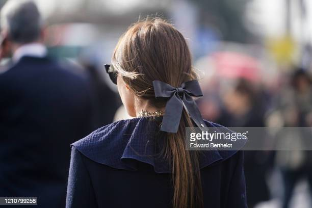 Guest wears a bow tie on the hair, a ruffled blue dress, a golden necklace, outside Chanel, during Paris Fashion Week - Womenswear Fall/Winter...