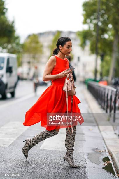 A guest wears a bracelet a red handkerchief hem flowing dress a beige bag a beige and black python pattern overtheknee pointy heeled boots outside...