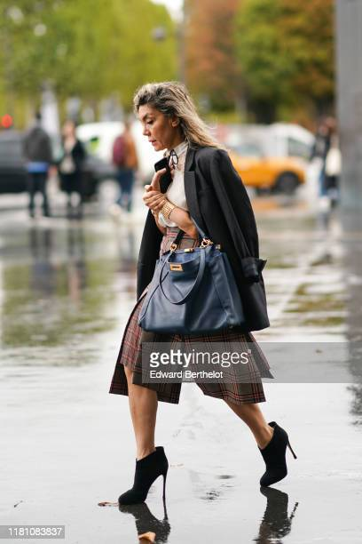 A guest wears a bracelet a white shirt with a white lace yoke a black jacket a navy blue bag a brown red and black checkered skirt black suede heeled...