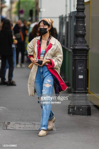 Guest wears a brown and beige striped scarf, a multicolored stones necklace, a pale blue ribbed shoulder-off top / t-shirt, a long beige oversized...