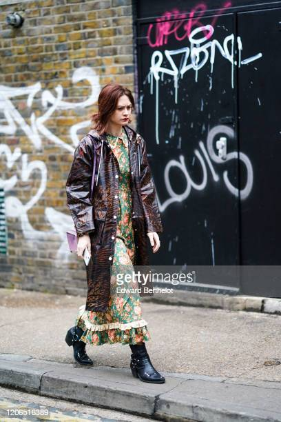 A guest wears a brown and black zebra print pattern trench coat a ruffled green floral print dress black leather pointy boots during London Fashion...
