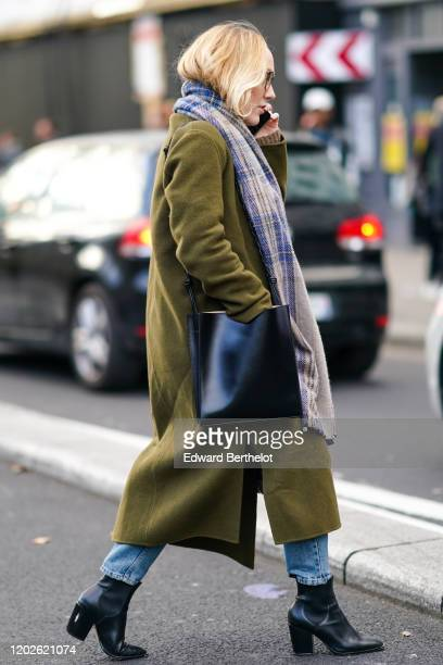A guest wears a brown and blue checkered scarf a black bag a khaki wool coat blue jeans black pointy ankleboots with block heels outside Paul Smith...