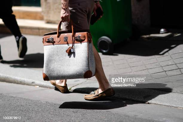 A guest wears a brown and gray Hermes bag outside Thom Browne during Paris Fashion Week Menswear SpringSummer 2019 on June 23 2018 in Paris France