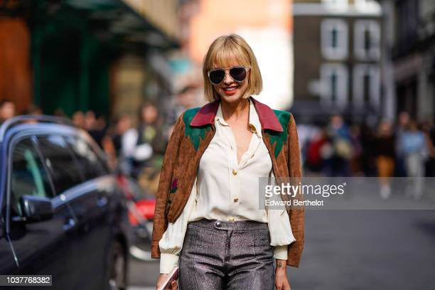 A guest wears a brown and red suede jacket with burgundy collar a white shirt gray pants snake print shoes during London Fashion Week September 2018...