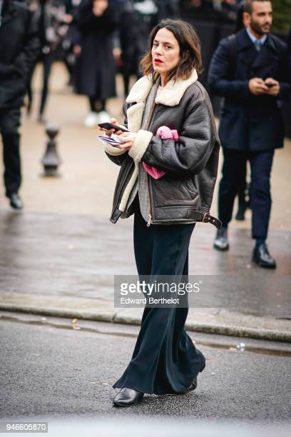 A guest wears a brown aviator jacket with sheep woo flare pants outside Dior during Paris Fashion Week Menswear Fall Winter 20182019 on January 20...