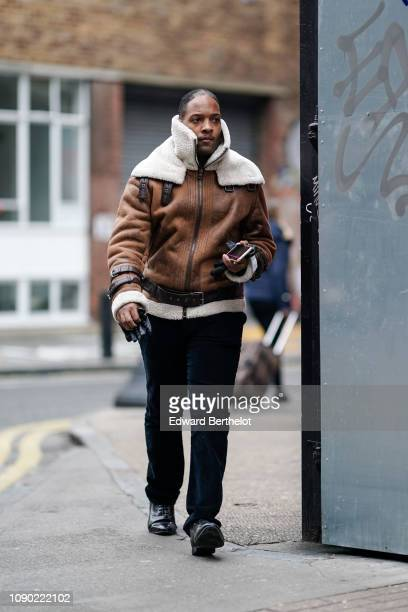 A guest wears a brown aviator jacket with sheep wool inner lining during London Fashion Week Men's January 2019 on January 05 2019 in London England