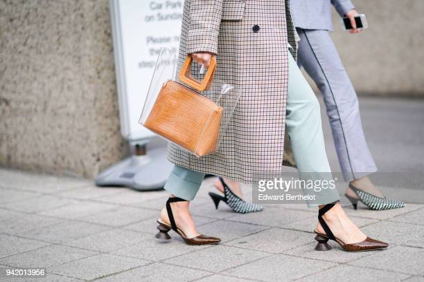 A guest wears a brown bag during London Fashion Week February 2018 on February 18 2018 in London England