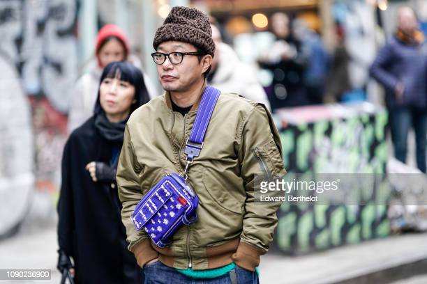 A guest wears a brown beanie hat a khaki bomber jacket a blue bag during London Fashion Week Men's January 2019 on January 05 2019 in London England
