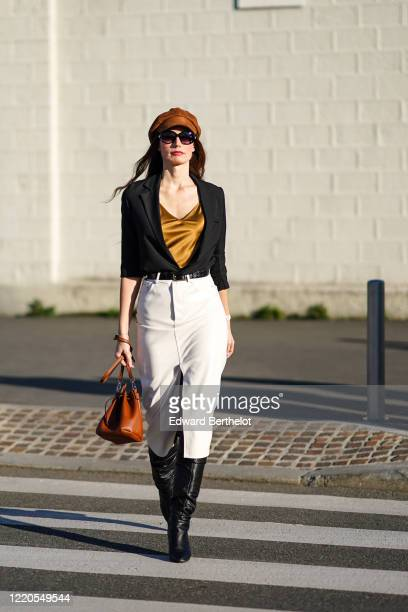 Guest wears a brown beret hat, a black jacket, a brown silky lustrous shiny v-neck low-neck top, a belt, a white slit skirt, black leather boots, a...