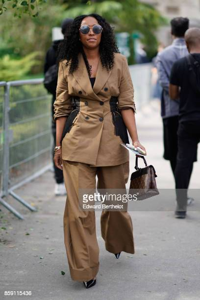 A guest wears a brown blaze brown large pants a Vuitton bag outside Issey Miyake during Paris Fashion Week Womenswear Spring/Summer 2018 on September...