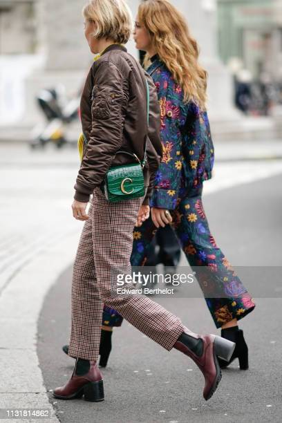 Guest wears a brown bomber jacket, a green alligator pattern bag, brown checkered pants, brown boots ; a guest wears a multicolor floral embroidered...