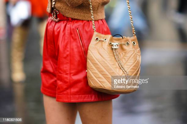 Guest wears a brown Chanel bag, a red leather skirt, outside Chanel, during Paris Fashion Week - Womenswear Spring Summer 2020, on October 01, 2019...