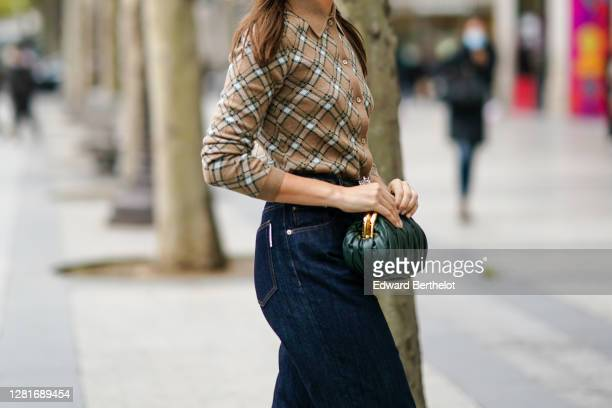 A guest wears a brown checked cardigan a green leather Miu Miu bag jeans outside Miu Miu during Paris Fashion Week Womenswear Spring Summer 2021 on...
