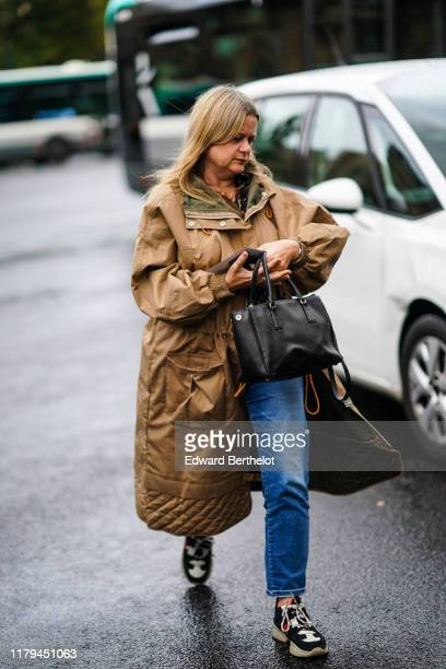A guest wears a brown coat a black leather bag blue denim jeans pants sneakers outside Miu Miu during Paris Fashion Week Womenswear Spring Summer...