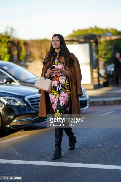 Guest wears a brown coat, a floral print colored dress, a bag, black leather boots, outside Prada, during Milan Fashion Week Fall/Winter 2020-2021 on...