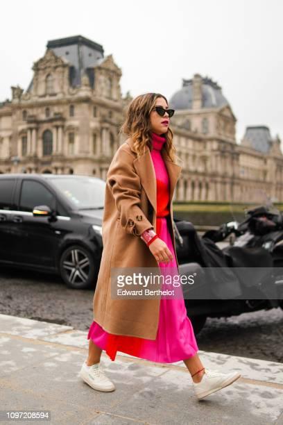 Guest wears a brown coat, a pink dress, a turtleneck wool top, outside Kenzo, during Paris Fashion Week - Menswear F/W 2019-2020, on January 20, 2019...