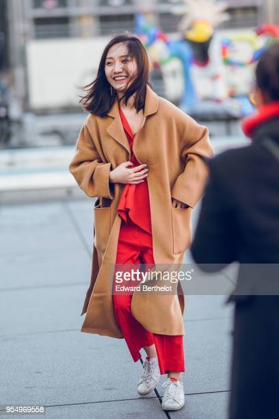 A guest wears a brown coat a red top red cropped pants white sneakers outside Off White during Paris Fashion Week Menswear Fall Winter 20182019 on...