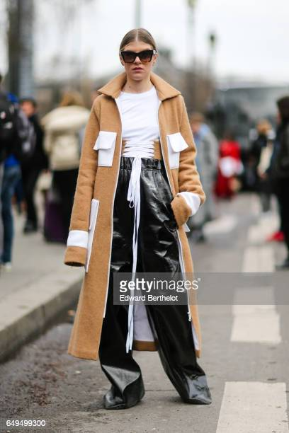 A guest wears a brown coat a white top and black flared vinyl pants outside the Chanel show during Paris Fashion Week Womenswear Fall/Winter...