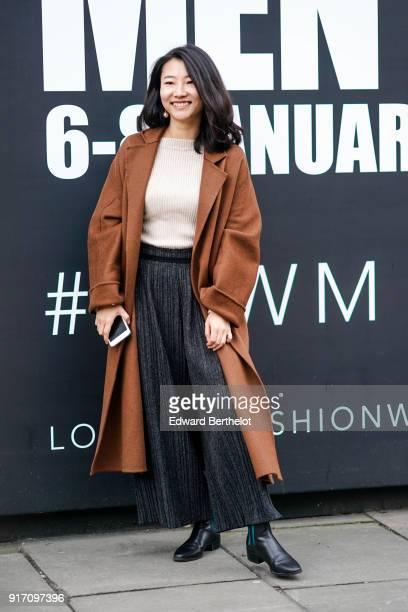 A guest wears a brown coat a white top flare pants black leather shoes holds a smartphone during London Fashion Week Men's January 2018 at on January...