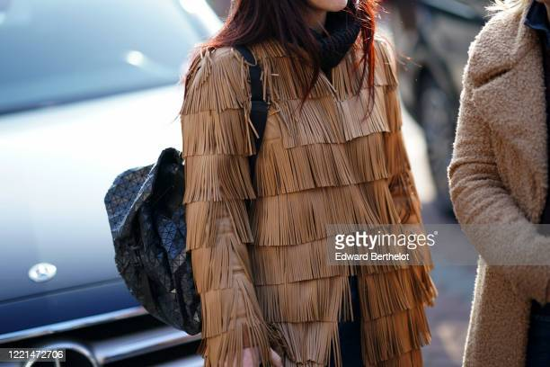 A guest wears a brown coat with fringes outside Gucci during Milan Fashion Week Fall/Winter 20202021 on February 19 2020 in Milan Italy