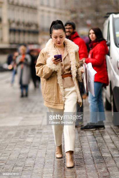 A guest wears a brown coat with sheep wool inner lining a beige jacket white pants outside Louis Vuitton during aris Fashion Week Menswear Fall...