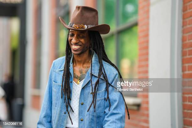 Guest wears a brown cow-boy hat with a feather, a blue denim jacket, a white V-neck braided wool pullover, a gold chain pendant necklace, outside the...