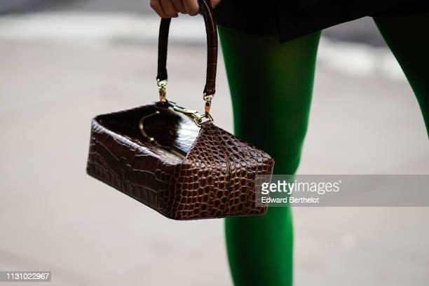 Guest wears a brown crocodile pattern handbag, during London Fashion Week February 2019 on February 19, 2019 in London, England.