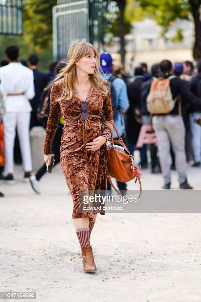 A guest wears a brown dress brown boots outside Valentino during Paris Fashion Week Womenswear Spring/Summer 2019 on September 30 2018 in Paris France