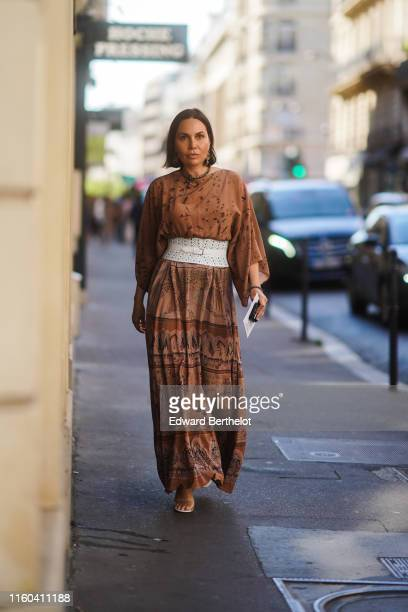 A guest wears a brown dress wit printed features a white large belt earrings outside Valentino during Paris Fashion Week Haute Couture Fall/Winter...