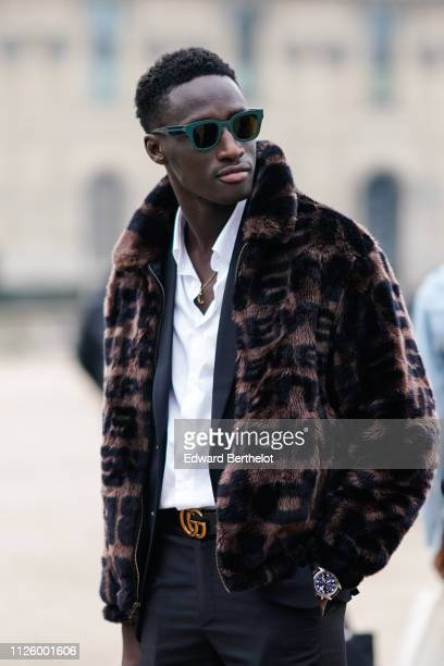 A guest wears a brown faux fur coat a white shirt a Gucci belt a watch sunglasses outside Kenzo during Paris Fashion Week Menswear F/W 20192020 on...