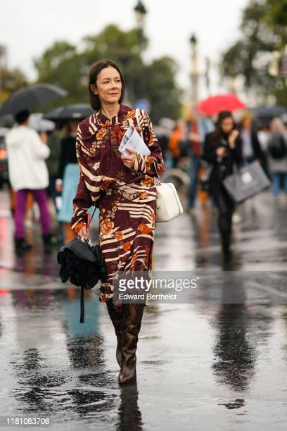 Guest wears a brown floral print long sleeves dress, a white bag, a brown and black python pattern pointy heeled knee-high boots, outside Chanel,...