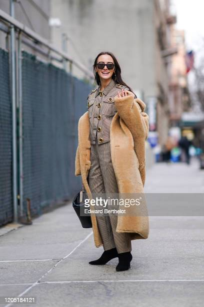 Guest wears a brown fluffy long coat, a gray jacket with golden large buttons, pants, black pointy shoes, a leather bag, sunglasses, outside Tory...