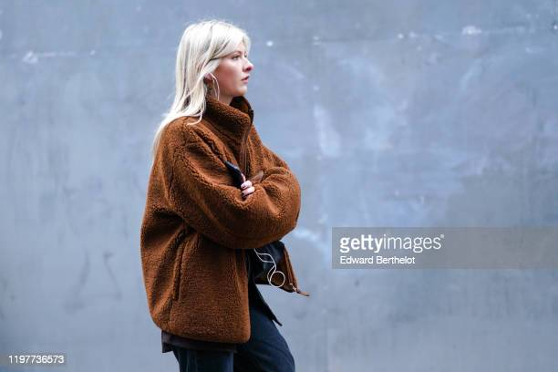 Guest wears a brown fluffy winter coat, during London Fashion Week Men's January 2020 on January 05, 2020 in London, England.