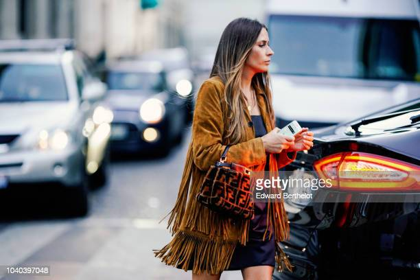 A guest wears a brown fringed jacket and a Fendi bag outside Ellery during Paris Fashion Week Womenswear Spring/Summer 2019 on September 25 2018 in...
