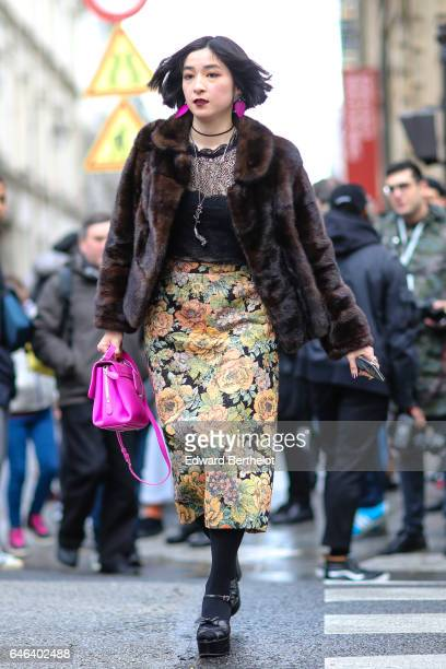 A guest wears a brown fur coat a pink bag a black lace top and a floral print skirt outside the JOUR/NE show during Paris Fashion Week Womenswear...