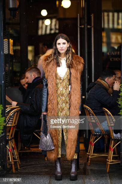 Guest wears a brown fur coat with black leather sleeves, a metallic bag, brown leather boots, a white shirt, a dress with printed argyle patterns,...