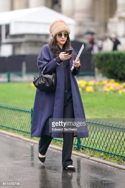 A guest wears a brown fur hat green circular sunglasses a blue coat a balck bag black flare pants black shoes holds a smartphone outside Chanel...