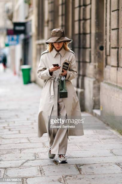 A guest wears a brown hat a beige trench coat beige wideleg pants grey and brown sneakers outside Nobi Talai during Paris Fashion Week Womenswear...