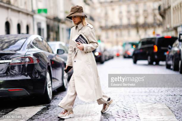 Guest wears a brown hat, a beige trench coat, beige wide-leg pants, grey and brown sneakers, outside Nobi Talai, during Paris Fashion Week Womenswear...
