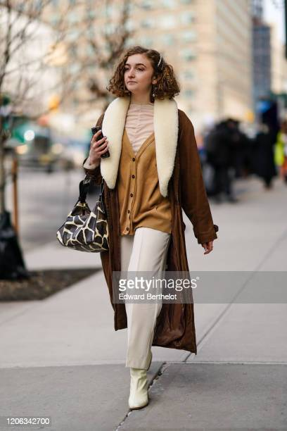 A guest wears a brown jacket a brown long coat with white fluffy collar a cow pattern printed bag white pants boots hair pin during New York Fashion...