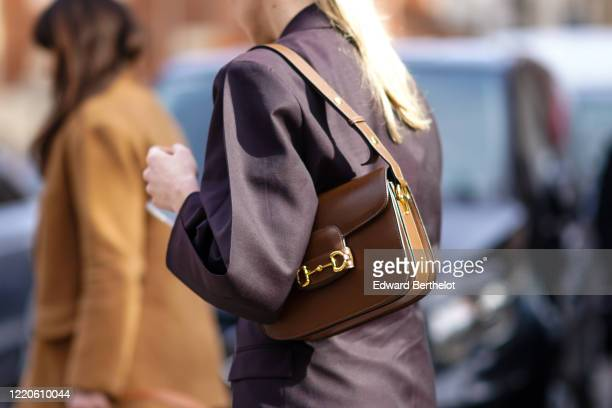 A guest wears a brown leather bag outside Koche x Pucci during Milan Fashion Week Fall/Winter 20202021 on February 20 2020 in Milan Italy