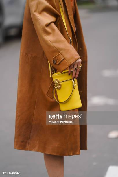 Guest wears a brown leather coat, a yellow cylinder shaped bag, outside Gauchere, during Paris Fashion Week - Womenswear Fall/Winter 2020/2021 on...
