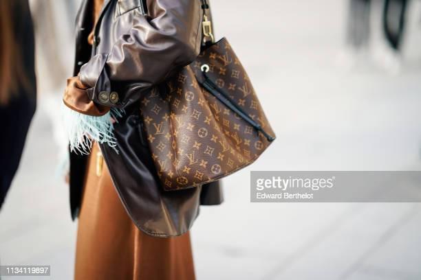 Guest wears a brown leather jacket, a Louis Vuitton monogram bag, outside Louis Vuitton, during Paris Fashion Week Womenswear Fall/Winter 2019/2020,...